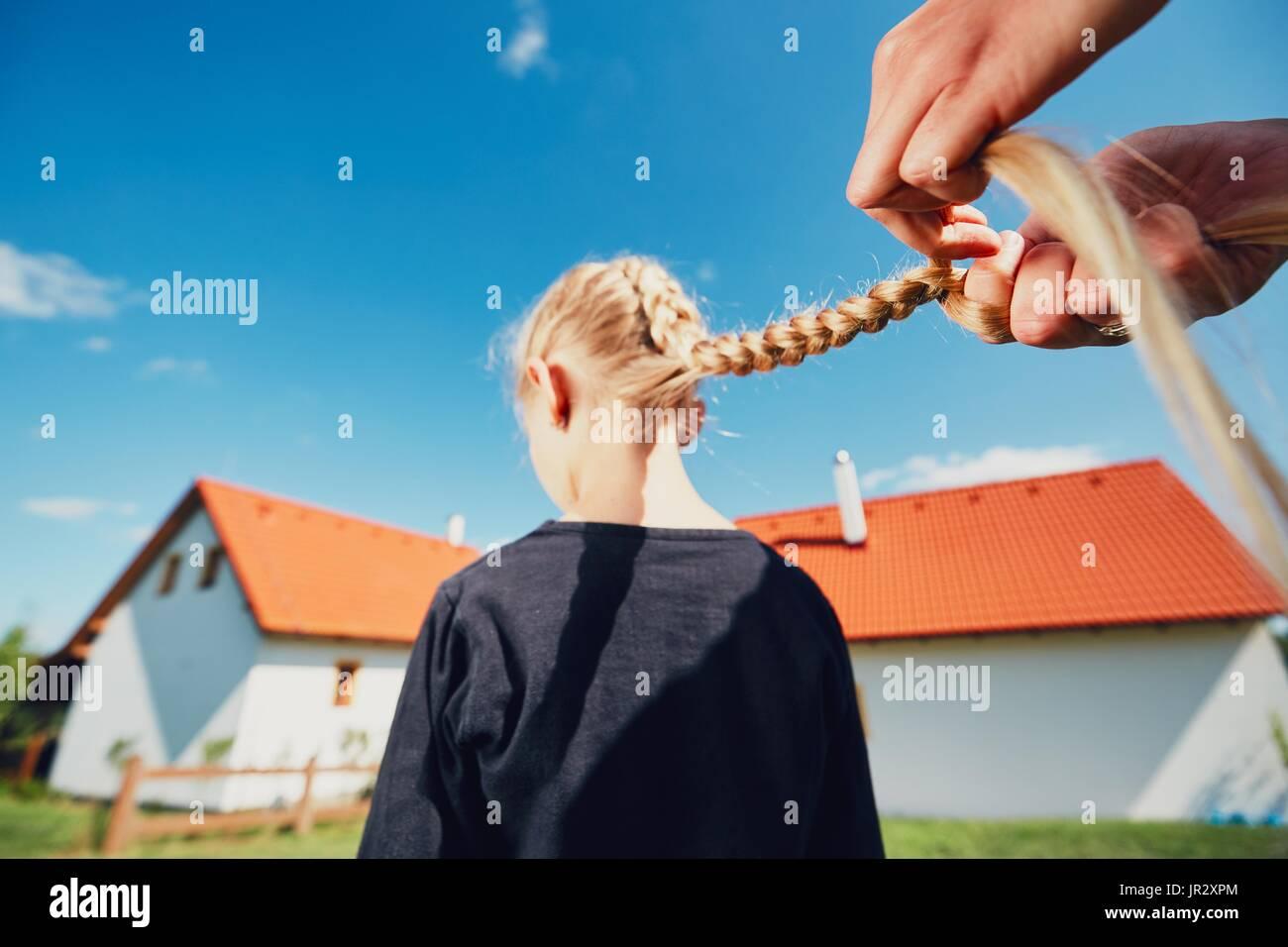 Junge Frau Haarflechten des kleinen Mädchens auf dem Garten auf dem Lande machen. Stockbild