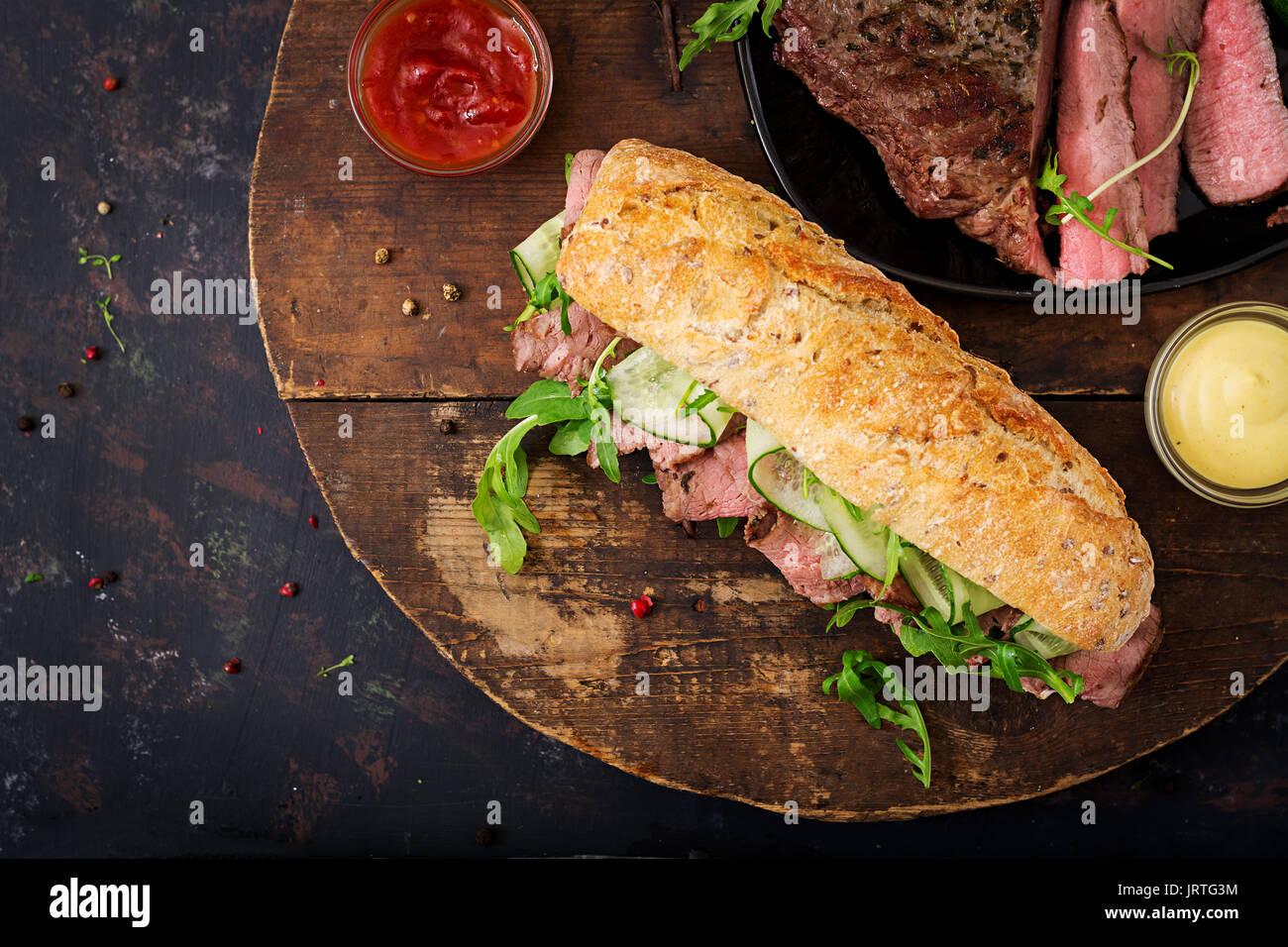 Sandwich von Vollkornbrot mit Roastbeef, Gurke und Rucola. Ansicht von oben. Flach. Stockbild