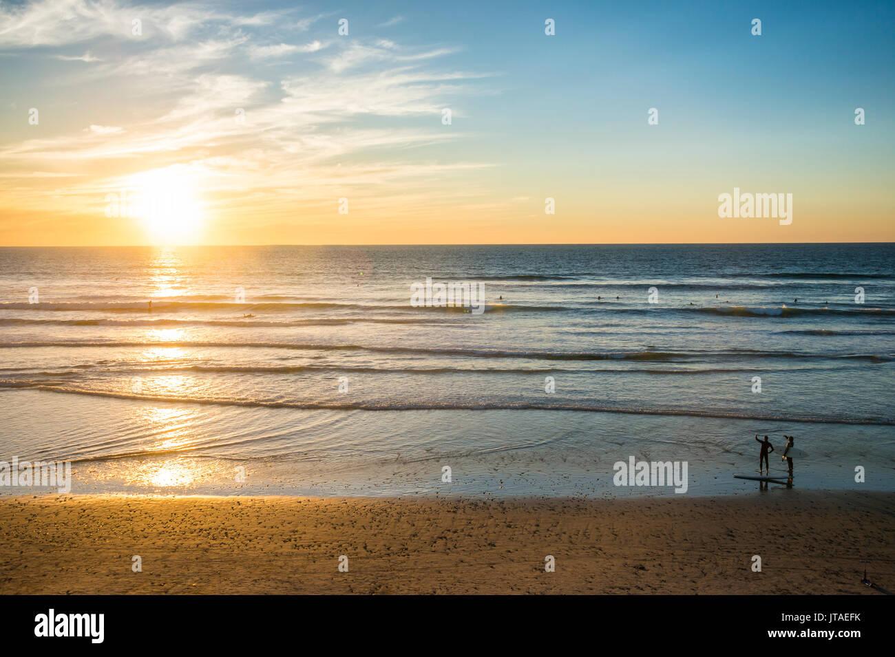 Paar in der Hintergrundbeleuchtung zu Fuß bei Sonnenuntergang, Del Mar, Kalifornien, Vereinigte Staaten von Stockbild