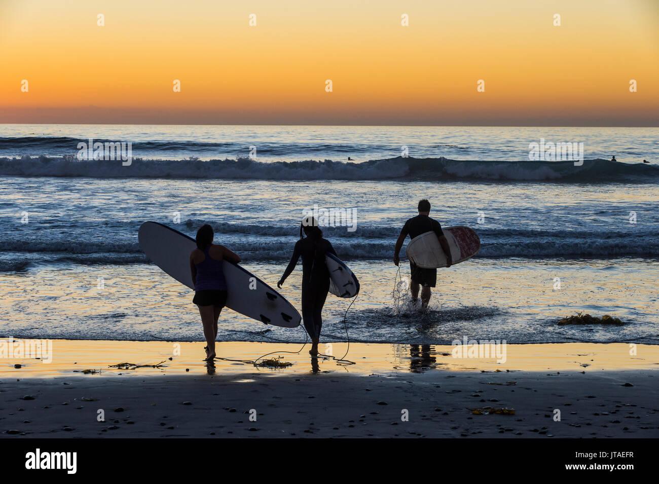 Surfer gehen mit ihren Surfboards im Meer bei Sonnenuntergang, Del Mar, Kalifornien, Vereinigte Staaten von Amerika, Stockbild
