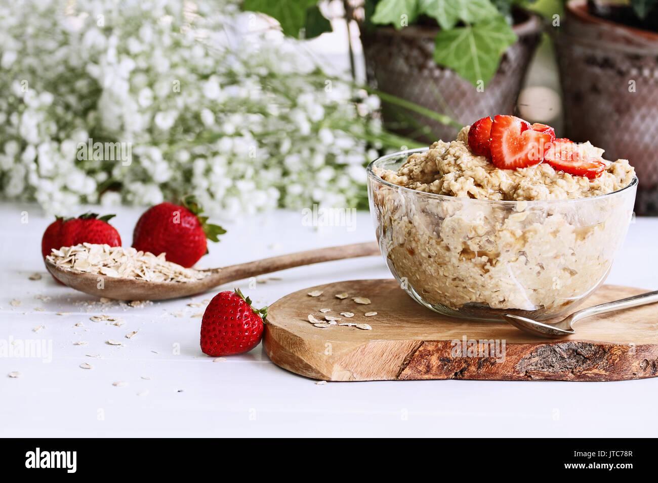 Warmes Frühstück der gesunden Haferflocken und herzförmige Erdbeeren. Selektiver Fokus mit extrem Stockbild