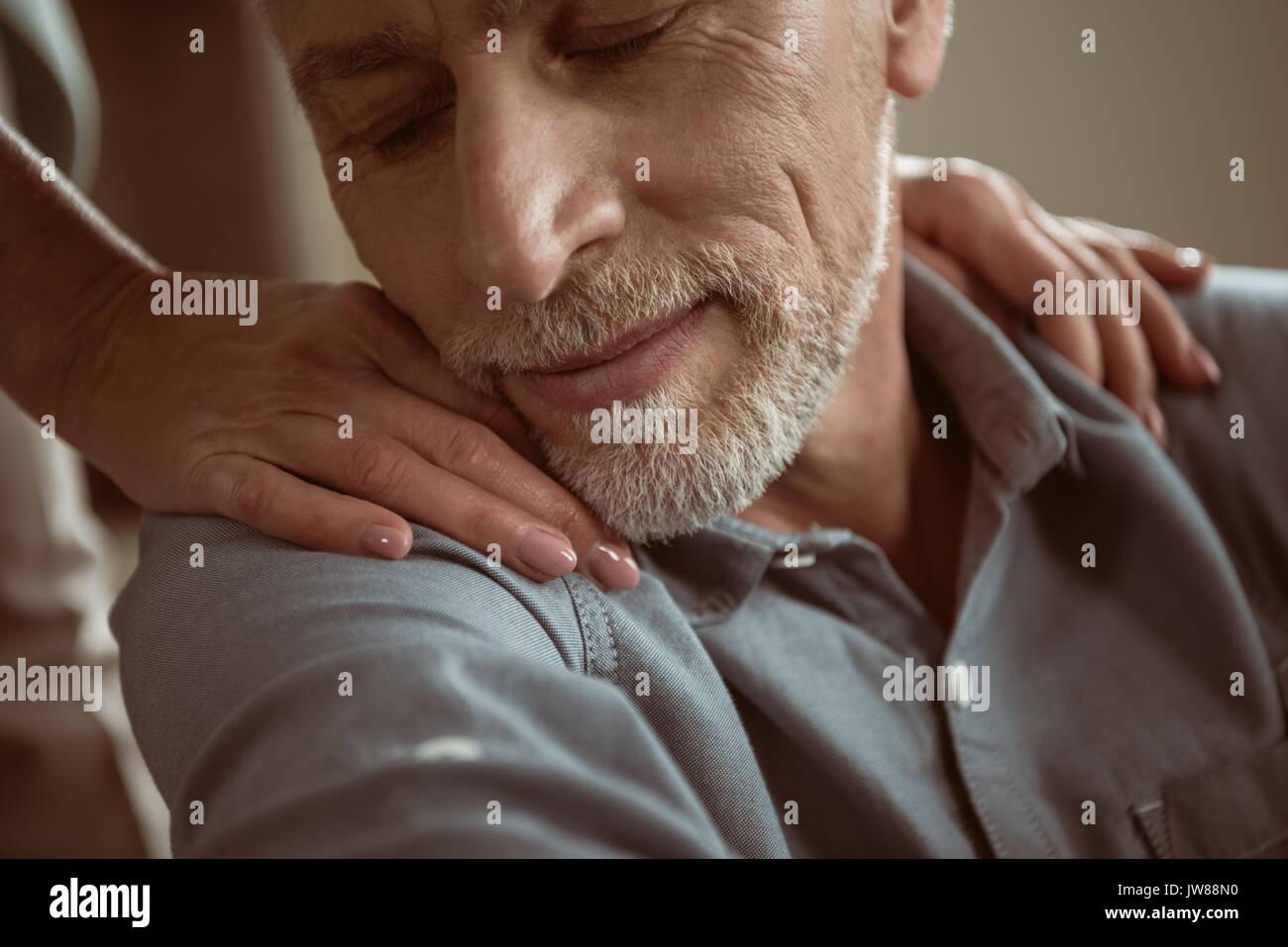 Zarte Frau, Hände auf den Schultern des Mannes mit geschlossenen Augen Stockbild