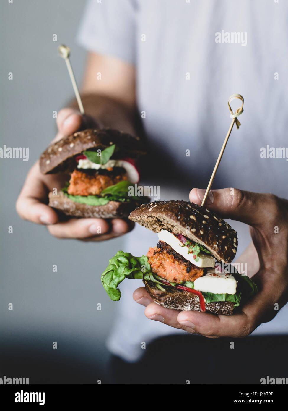 Junge hipster Holding vegetarische Karotte Tofu Burger. Detailansicht, selektiver Fokus Stockbild