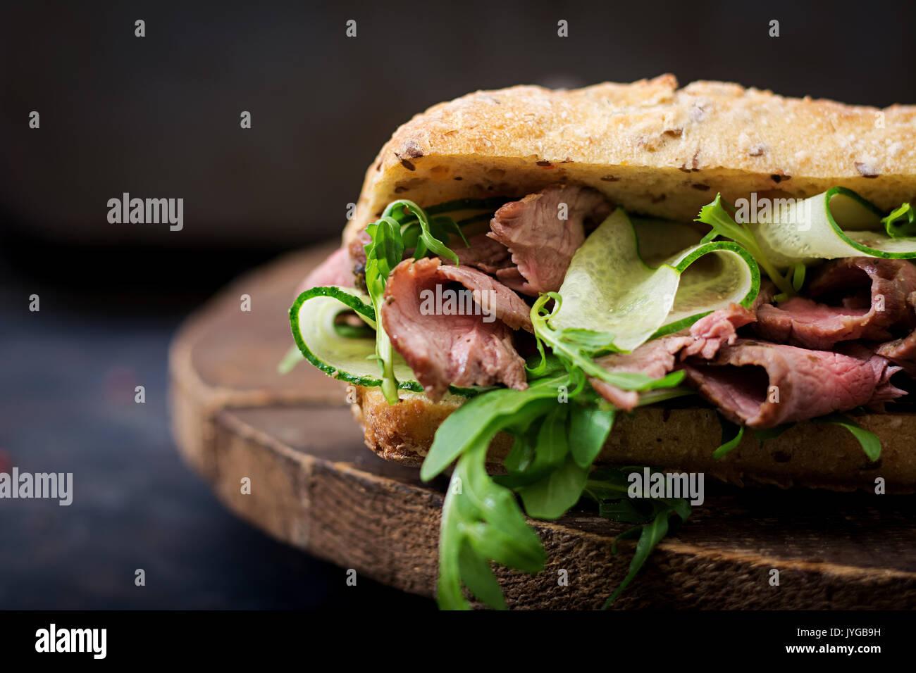 Sandwich von Vollkornbrot mit Roastbeef, Gurke und Rucola Stockbild