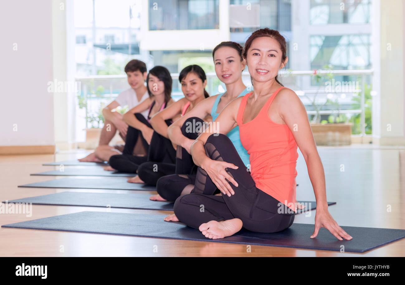 Yoga Klasse in Studio Zimmer, eine Gruppe von Menschen sitzt die Hälfte der Herr der Fische Posen, Entspannung Sport Stockfoto