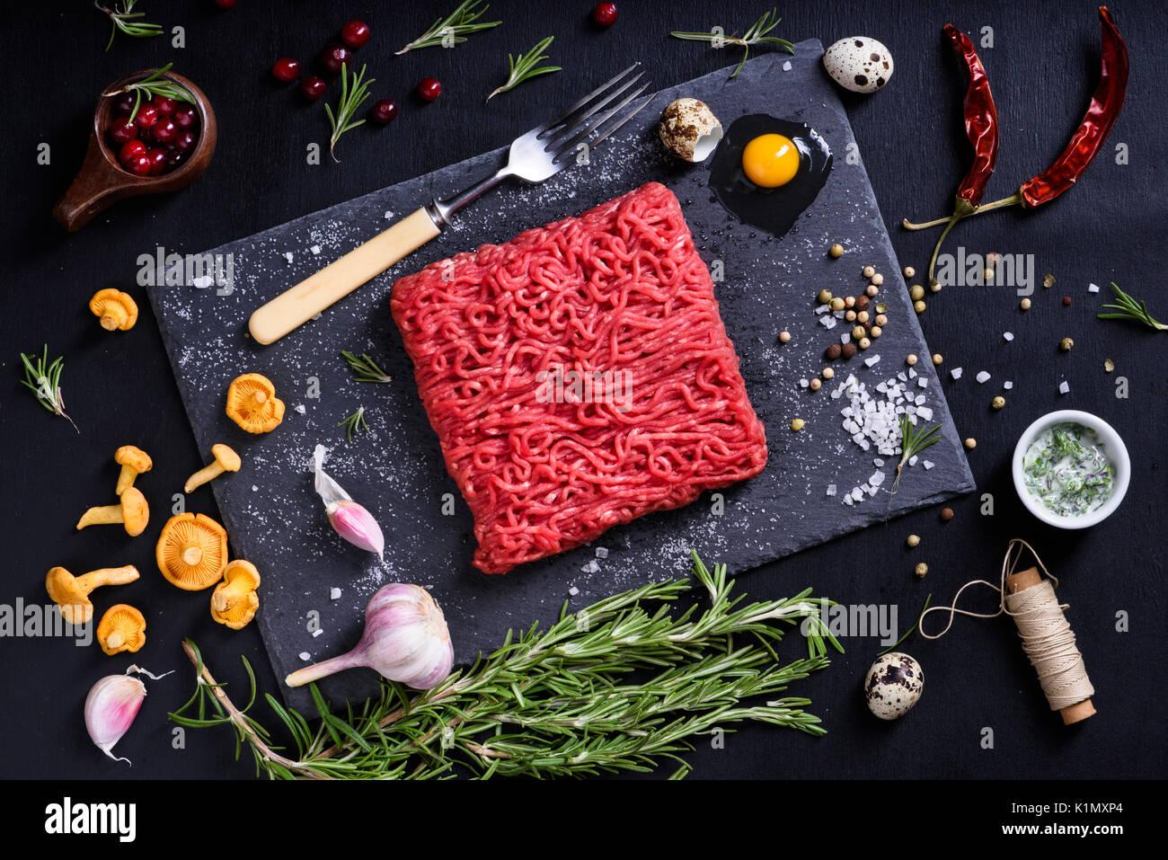Gehackte oder Hackfleisch mit Kräutern, Beeren und Pfifferlingen. Restaurant kochen Konzept. Ansicht von oben. Stockbild