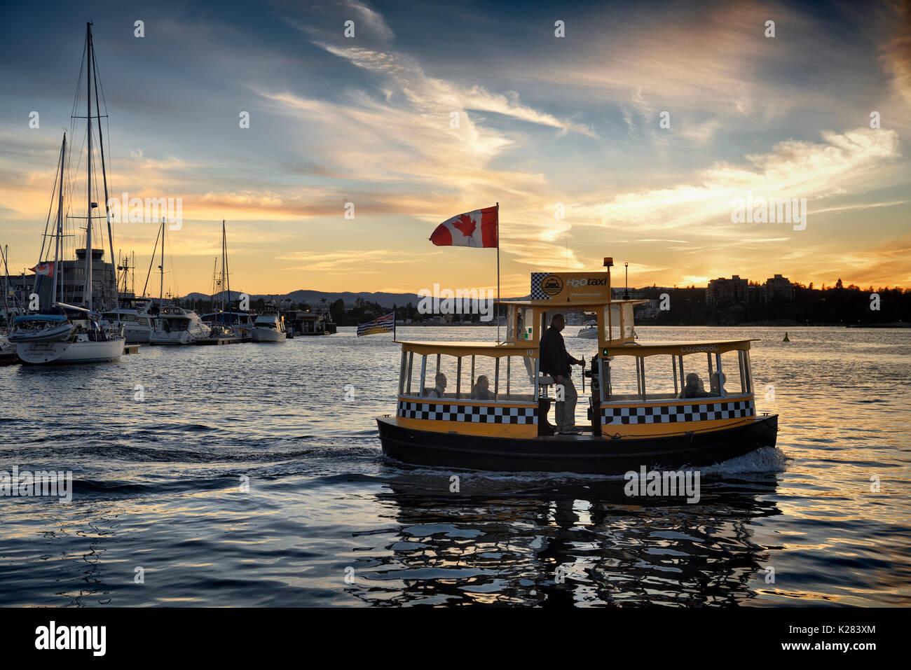 H2O Taxi Boot im Victoria Harbour in einem wunderschönen Sonnenuntergang Landschaft. Vancouver Island, BC, Stockbild