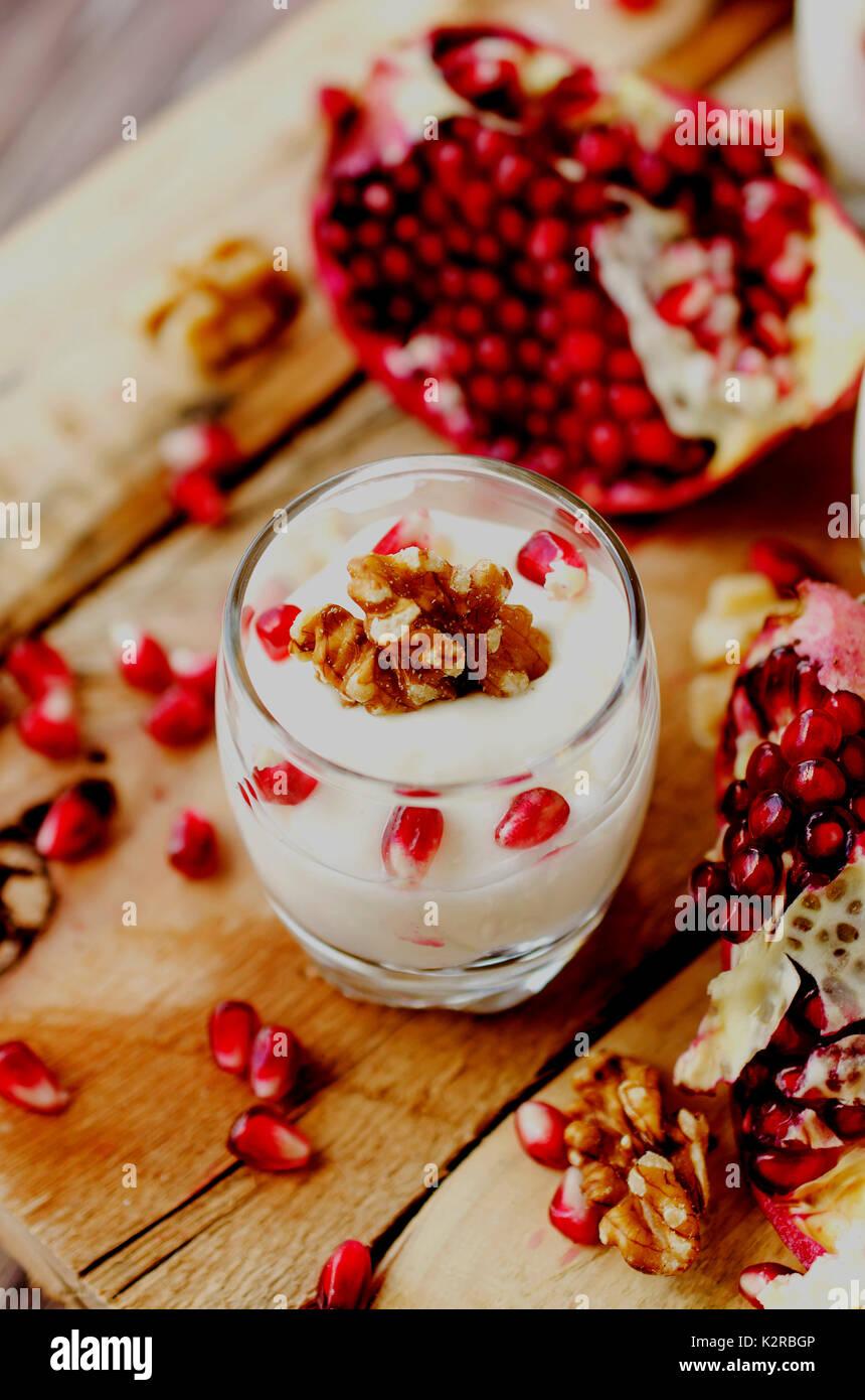Joghurt Dessert mit Walnüssen und frischer Granatapfel auf dem hölzernen Tisch, selektiver Fokus Stockbild