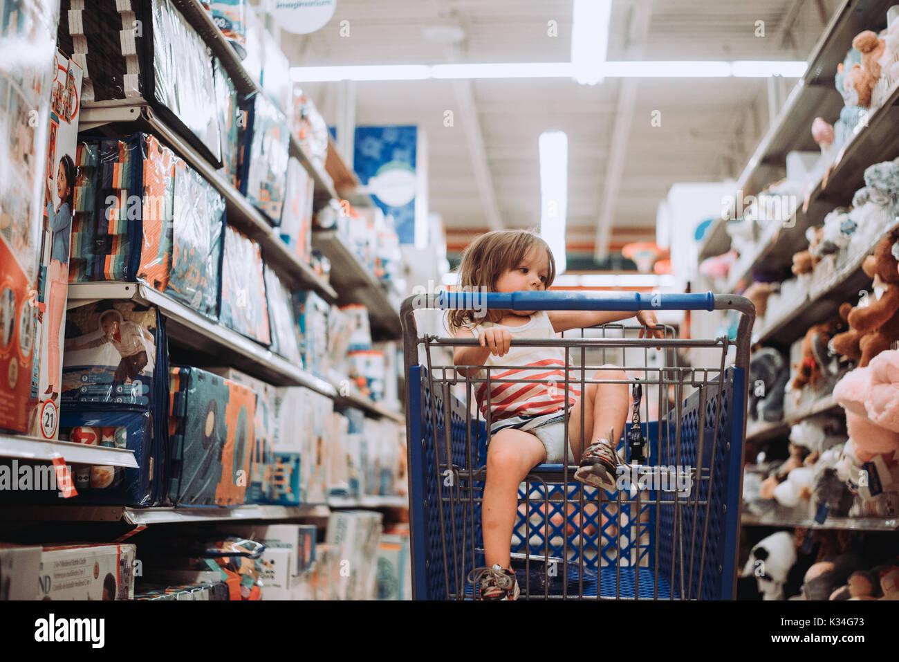 Ein Kleinkind sitzt in einem Warenkorb in einem Spielzeugladen. Stockbild