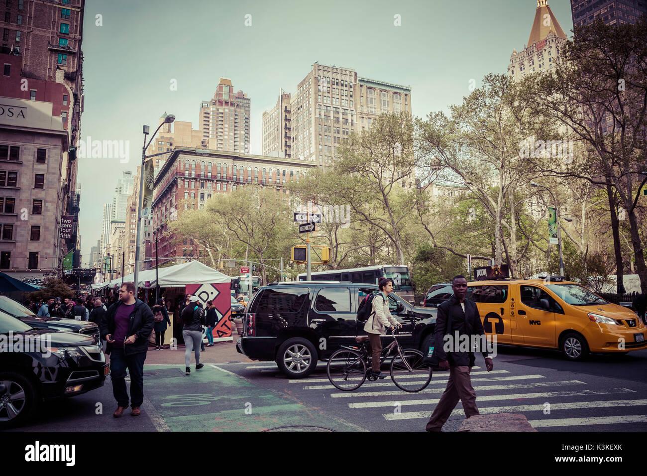 Typische NY Straßenbild, beschäftigt die Menschen auf einem Zebrastreifen und Verkehr an der 5th Avenue, Stockbild