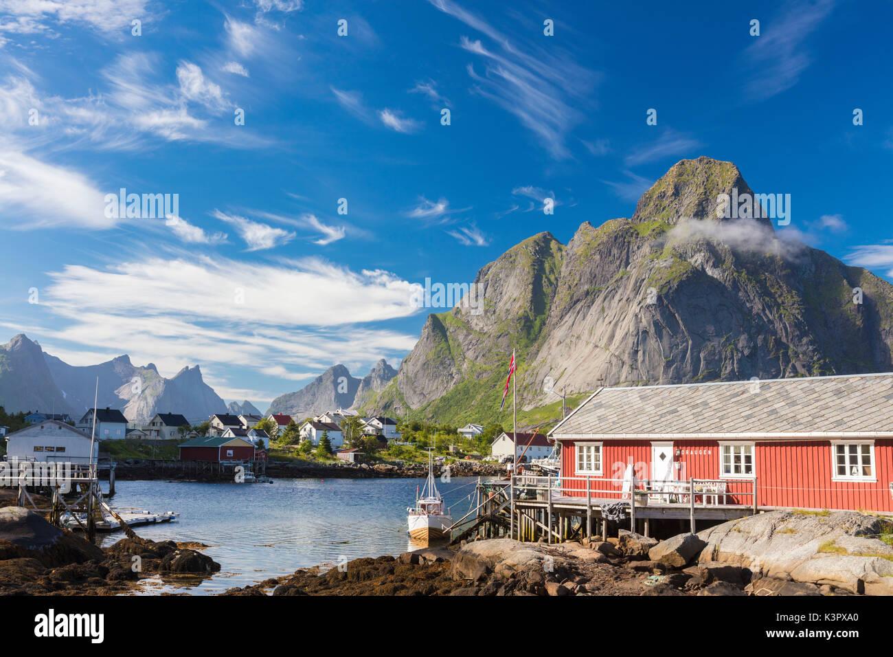 Typisches Haus der Fischer namens Rorbu von felsigen Gipfeln und blaues Meer Reine Moskenes Lofoten norwegen Europa Stockbild