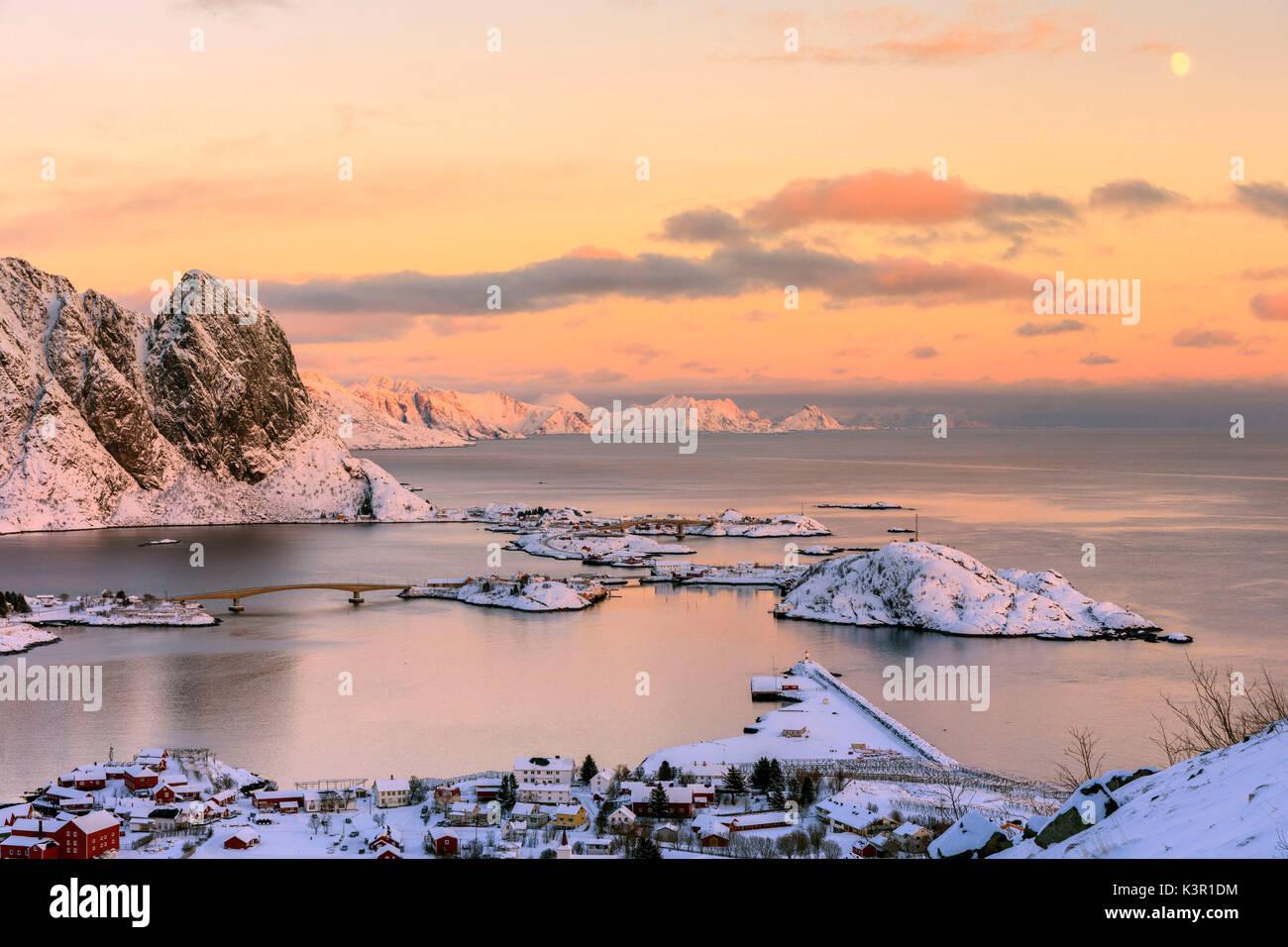 Die rosa Farben des Sonnenuntergangs und schneebedeckten Gipfeln umgeben die Fischerdörfer Reine Nordland Lofoten Stockbild