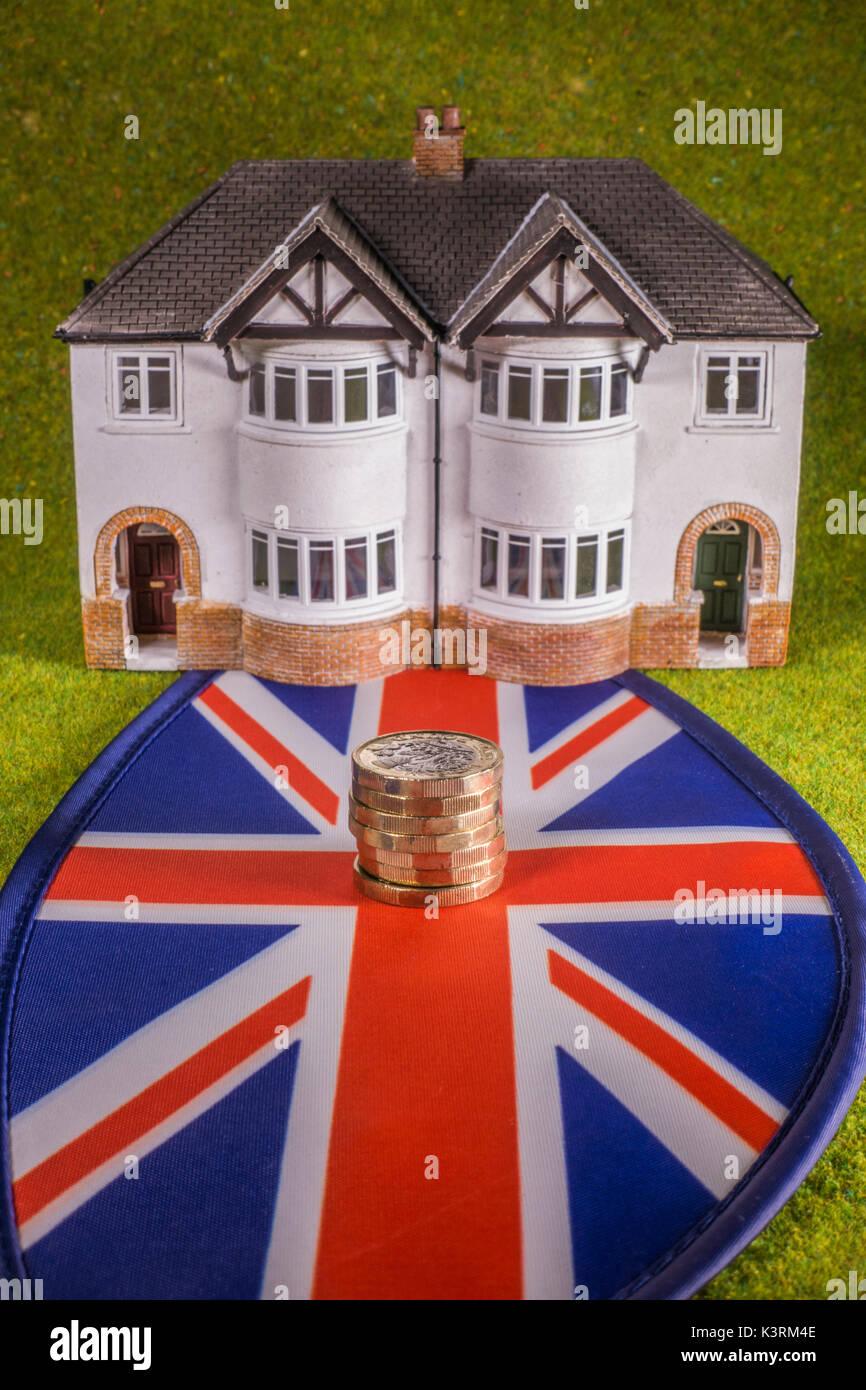 Modell Haus, Sterling Pound Münzen (mit neuen £1 Münze) und Union Jack, darzustellen, wie eine britische Stockbild