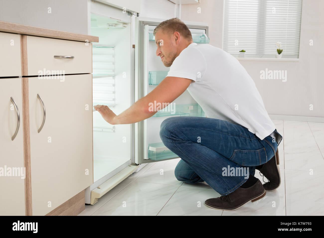 Kühlschrank Im Boden : Junger mann zusammengekauert auf dem boden und schauen in einem
