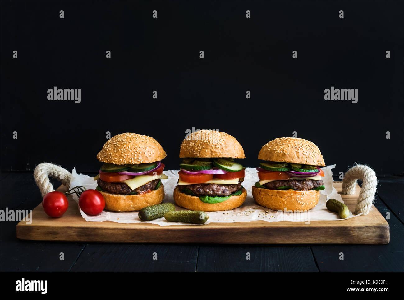 Frisches Rindfleisch Burger mit Käse, Gemüse, Gurken und würzigen Tomatensauce auf Papier über Stockbild