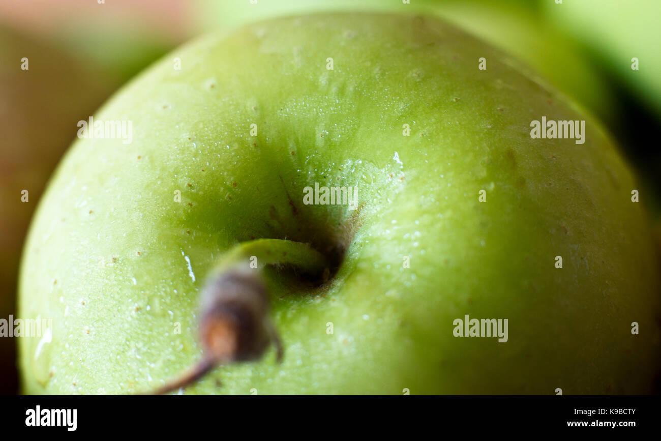 Ein grüner Apfel in der Tropfen Wasser. Makrofotos. Selektive konzentrieren. Stockbild