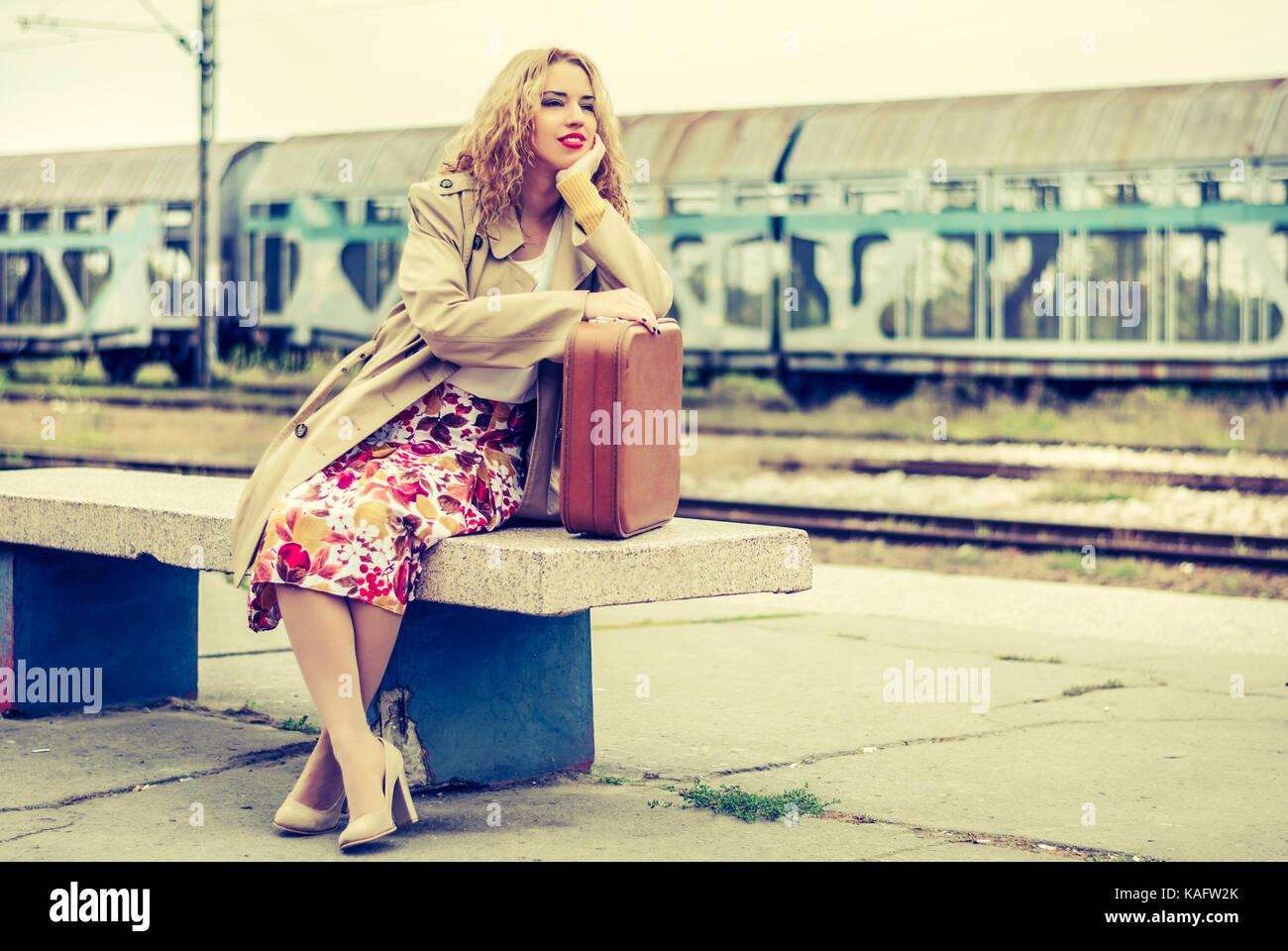 Frau mit einem Koffer und wartet, dass der Zug und Bahnhof. Junge Frau geht Stripe Sets und Einsamkeit Stockbild