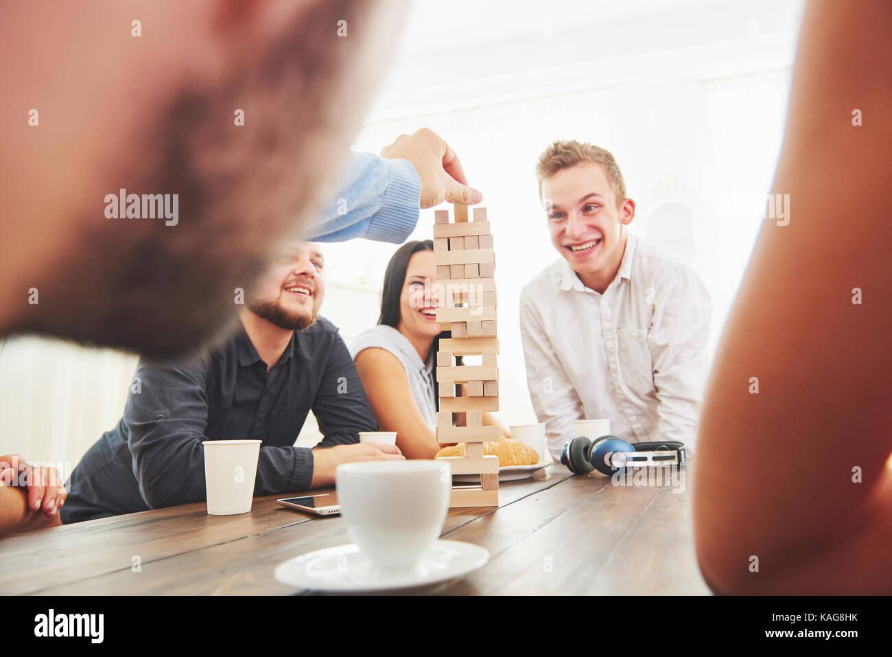 Gruppe der kreativen Freunde an den hölzernen Tisch sitzen. Menschen Spaß beim spielen brettspiel Stockbild