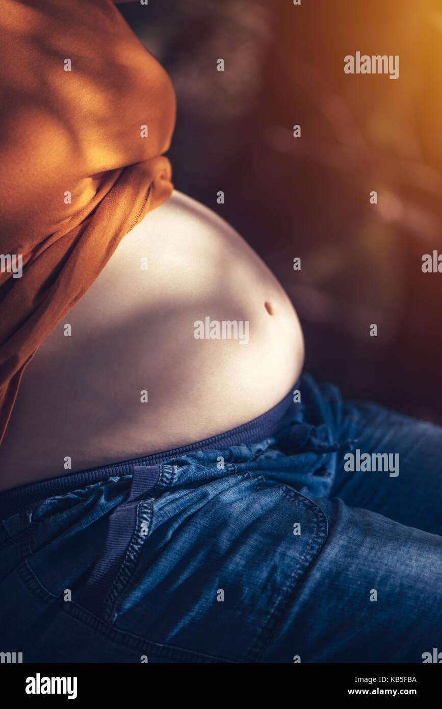 Schwangere Frau entspannen und sonnenbaden Bauch auf warmen Sommer Sonnenlicht, selektiven Fokus Stockbild