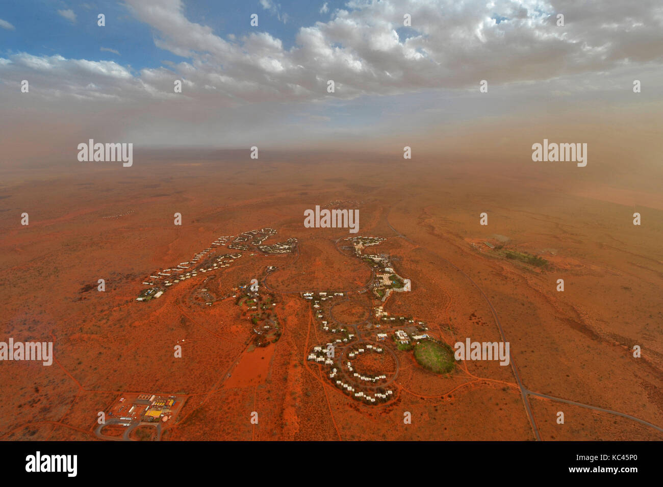 Luftaufnahme des Ortes yulara mit Uluru (ayres Rock) in Australiens Northern Territory, bei Sonnenuntergang. Stockbild