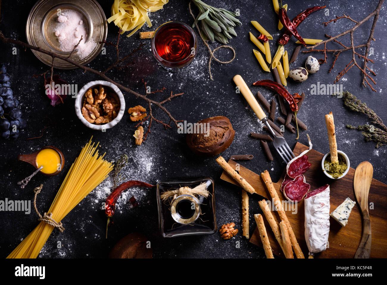 Vorspeise, Salami und Käse serviert mit Pasta und Rotwein auf dunklen Tisch. italienische Küche Zutaten. Stockbild