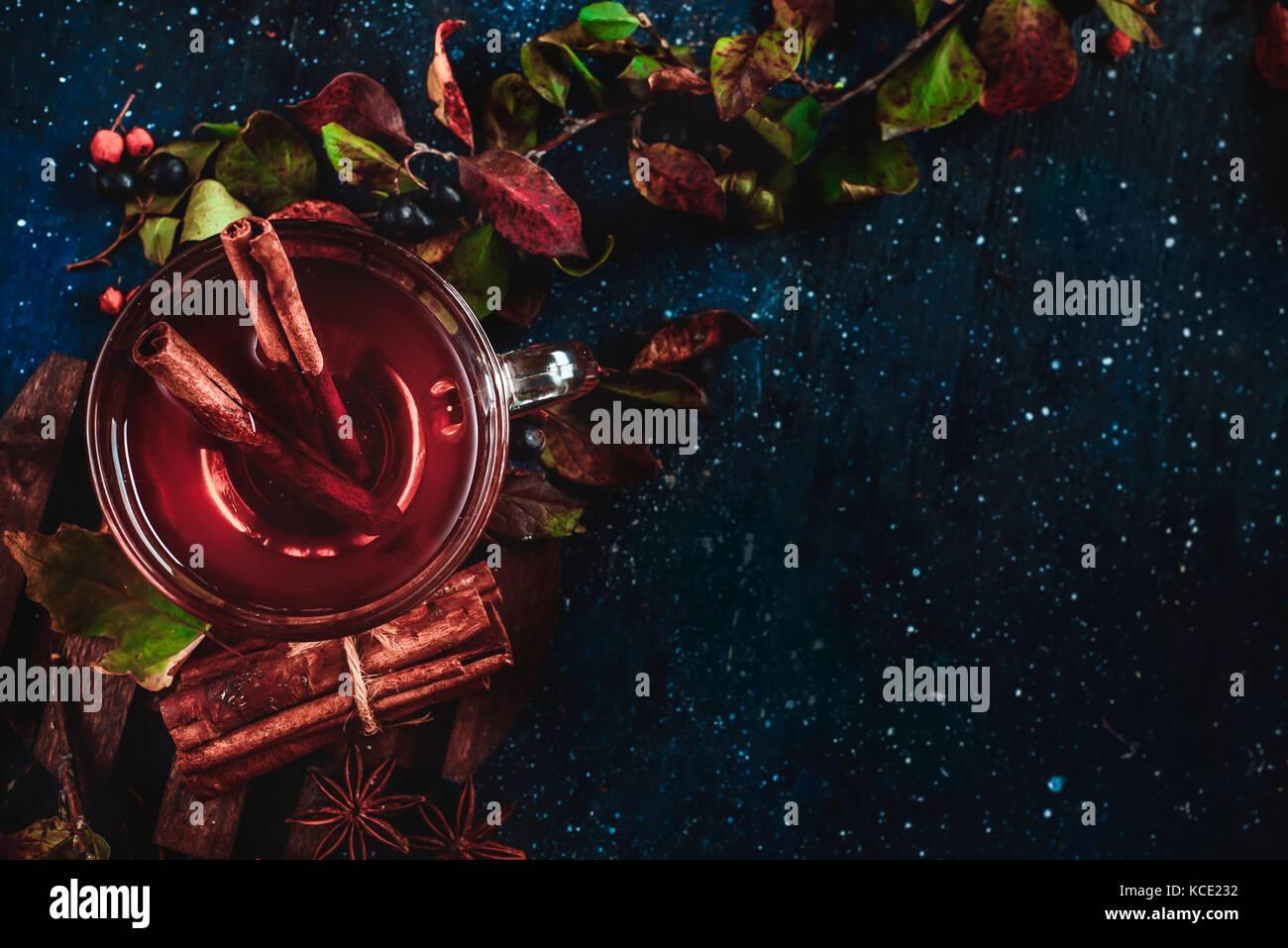Tasse Tee mit Zimt auf dunklem Hintergrund. Konzeptionelle stilisierte Food still life Herbst Blätter und Beeren. Stockbild