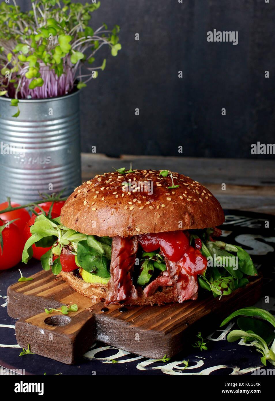 Frisches Fleisch Burger mit Grüns auf Holzbrett Stockbild