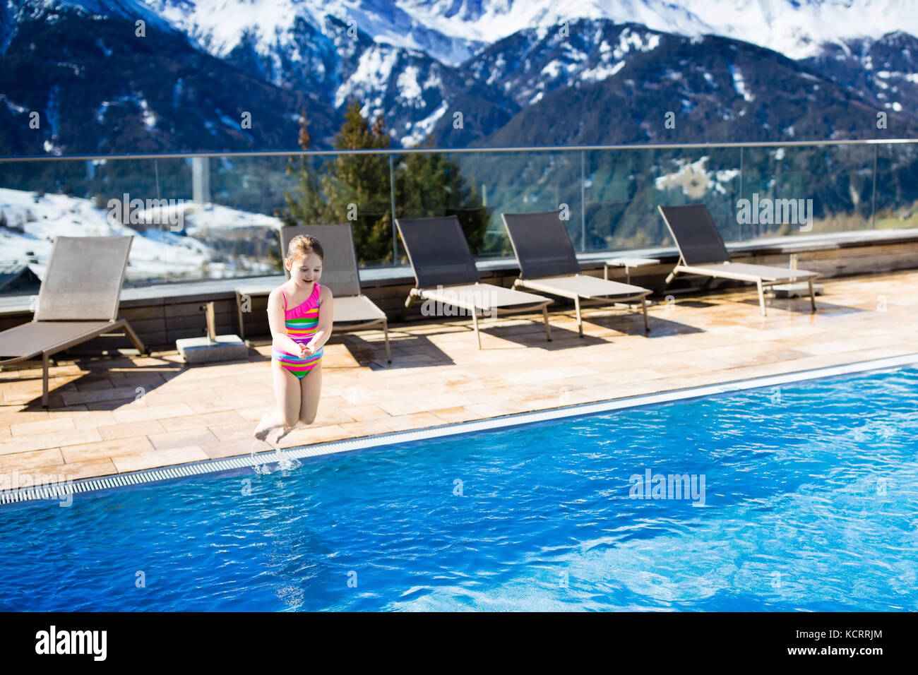 Kleine Kinder spielen im Außenpool des Luxus Alpine Resort in den ...