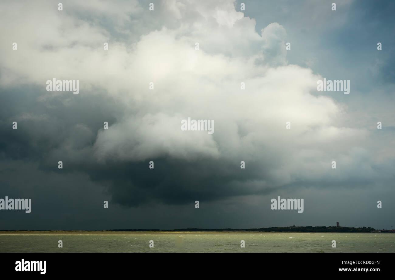 Dramatische Wolken auf der Insel Terschelling mit Leuchtturm Brandaris in Aussicht, west-terschelling, Friesland, Stockbild