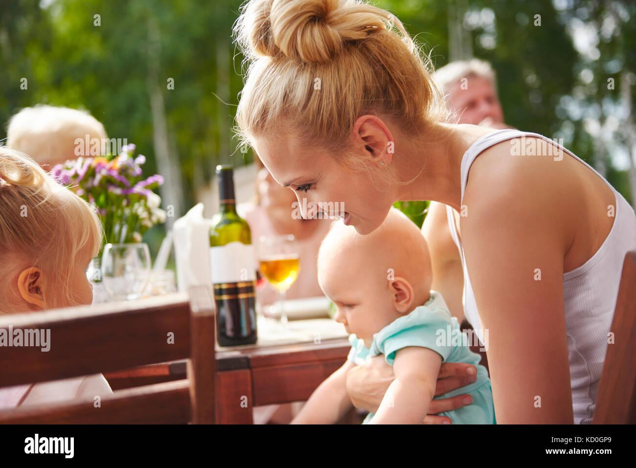 Junge Frau mit Baby und Kleinkind Töchter auf Terrasse Tisch Familie Mittagessen Stockbild