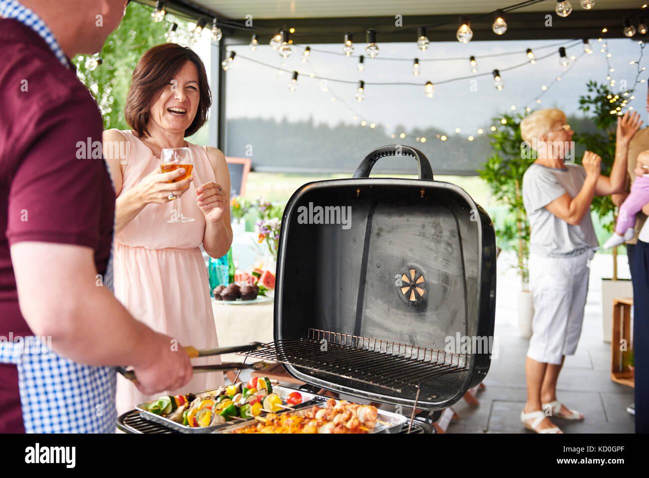 Der Mann und die Frau lacht beim Grillen auf der Terrasse bei Familie Mittagessen Stockbild