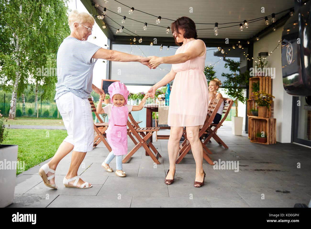 Senior und reife Frauen tanzen mit weiblichen Kleinkind bei Familie Mittagessen auf der Terrasse Stockbild