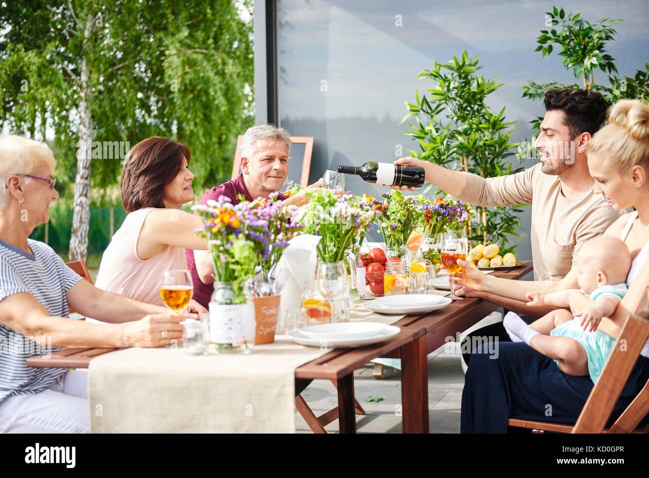 Drei Generationen der Familie zu Mittag und gießen Wein auf Tisch Stockbild