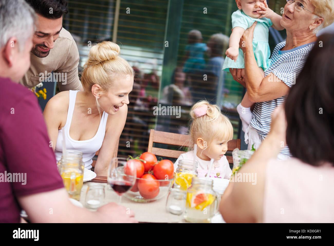 Drei generation Familie mit Baby und Kleinkind bei Familie Mittagessen auf der Terrasse Tisch Stockbild