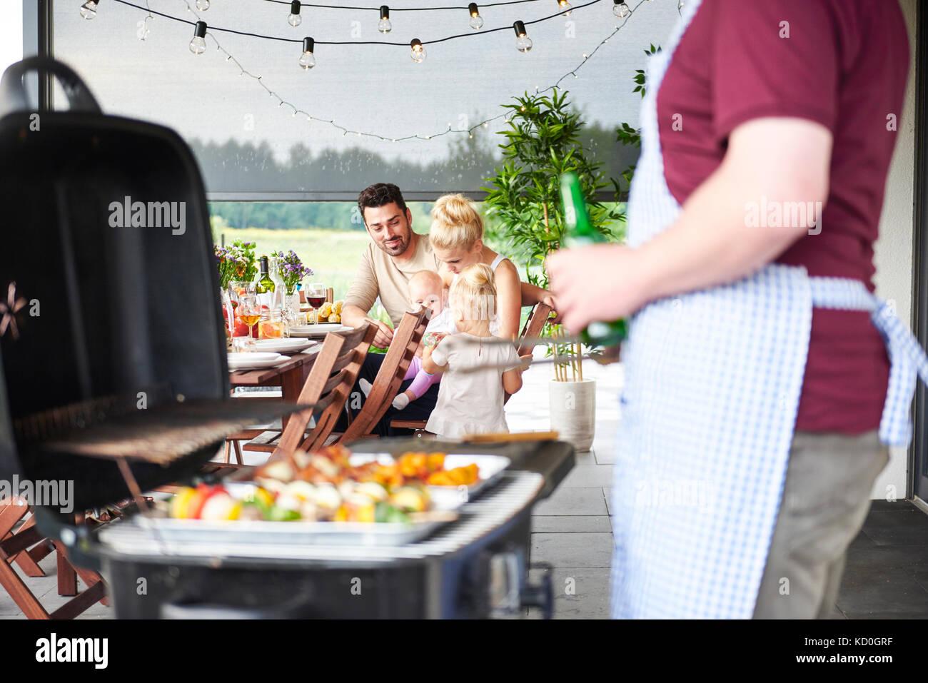 Man Grillen bei Familie Mittagessen auf der Terrasse Stockbild