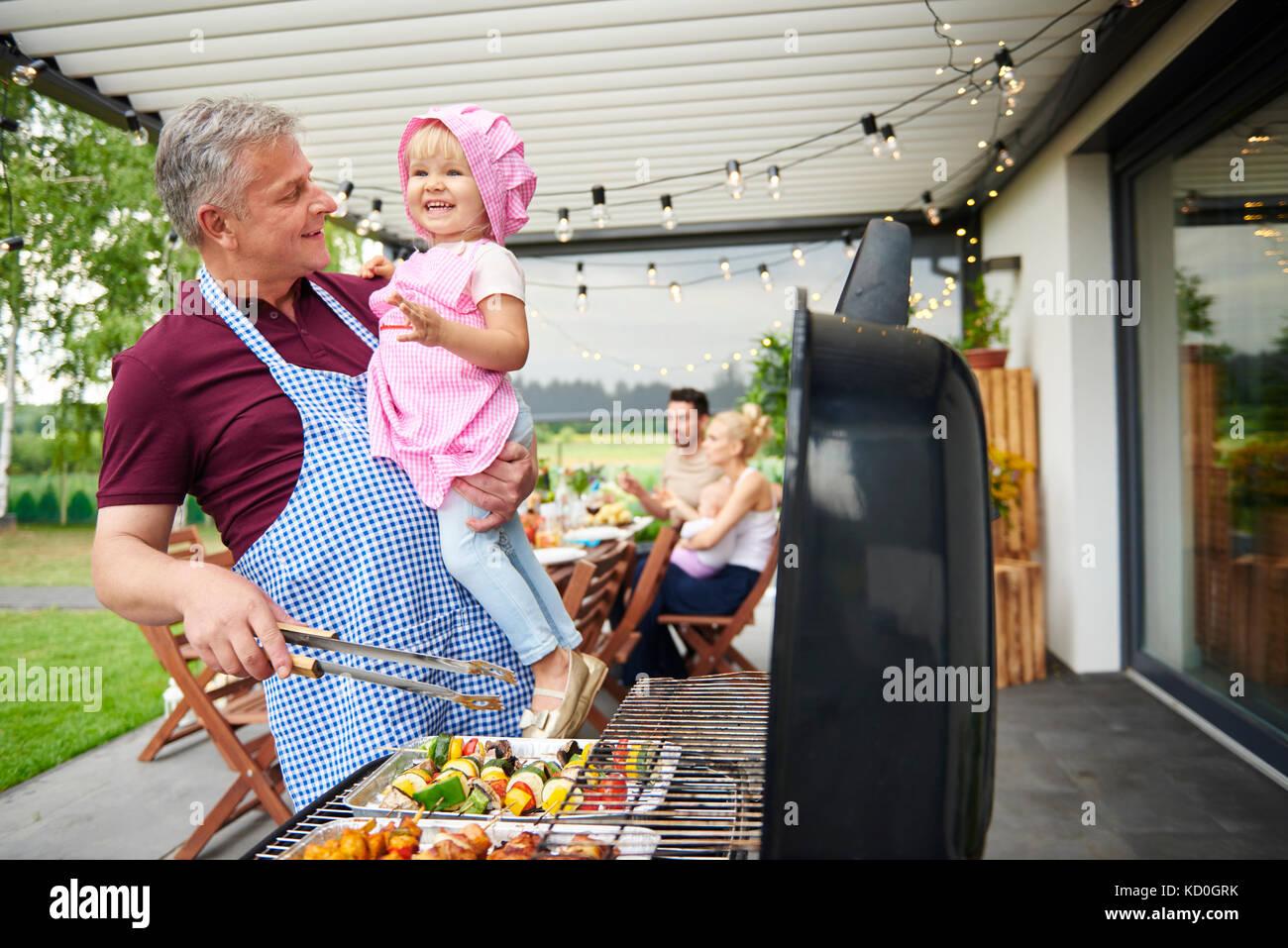 Reifer Mann mit Kleinkind Enkelin Grillen bei Familie Mittagessen auf der Terrasse Stockbild