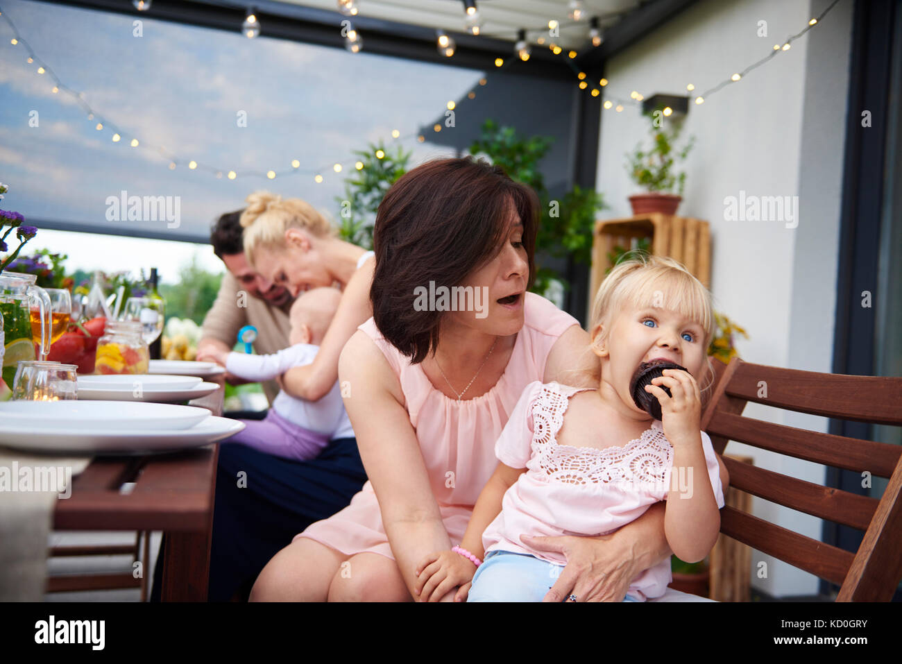 Reife Frau mit Kleinkind Enkelin essen Brownie bei Familie Mittagessen auf der Terrasse Stockbild