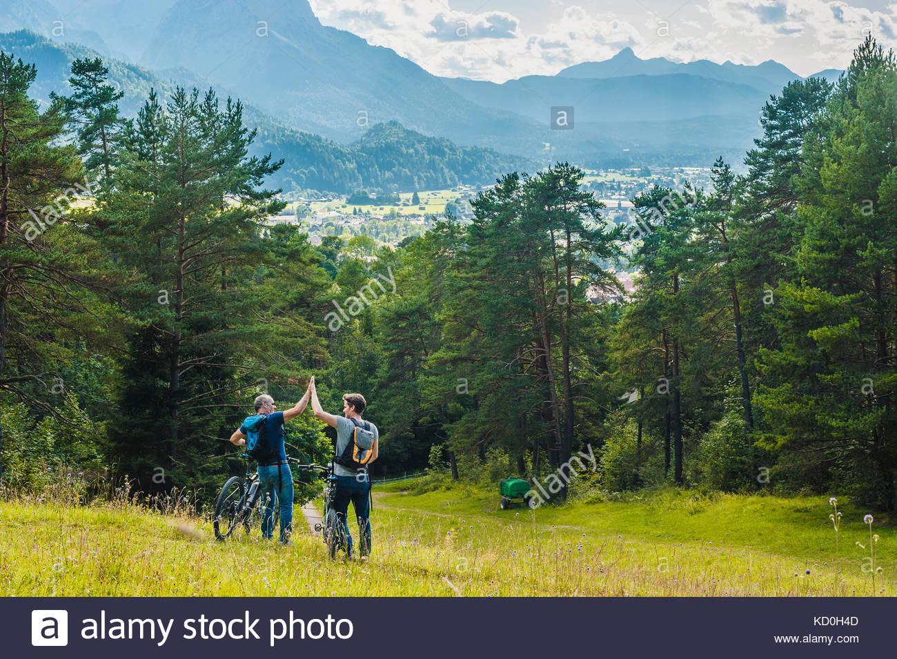 Vater und Sohn, in ländlicher Umgebung, Wandern mit Fahrrädern, die hohe fünf, elbsee, Bayern, Deutschland Stockbild