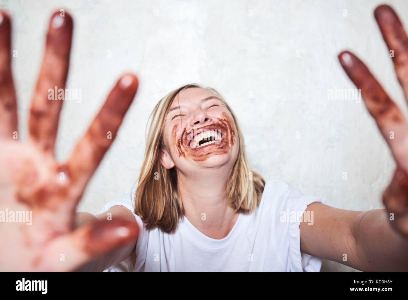 Portrait von Frau mit Schokolade an den Händen und um den Mund, Hände halten in Richtung Kamera, Lachen Stockbild