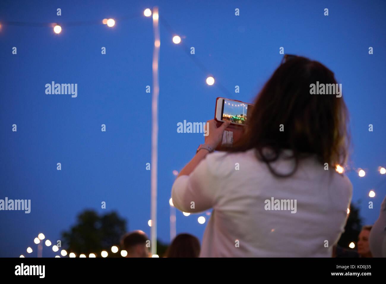 Reife Frau fotografieren blauer Himmel und Lichter in der Nacht Markt Festival in Park, London, UK Stockbild