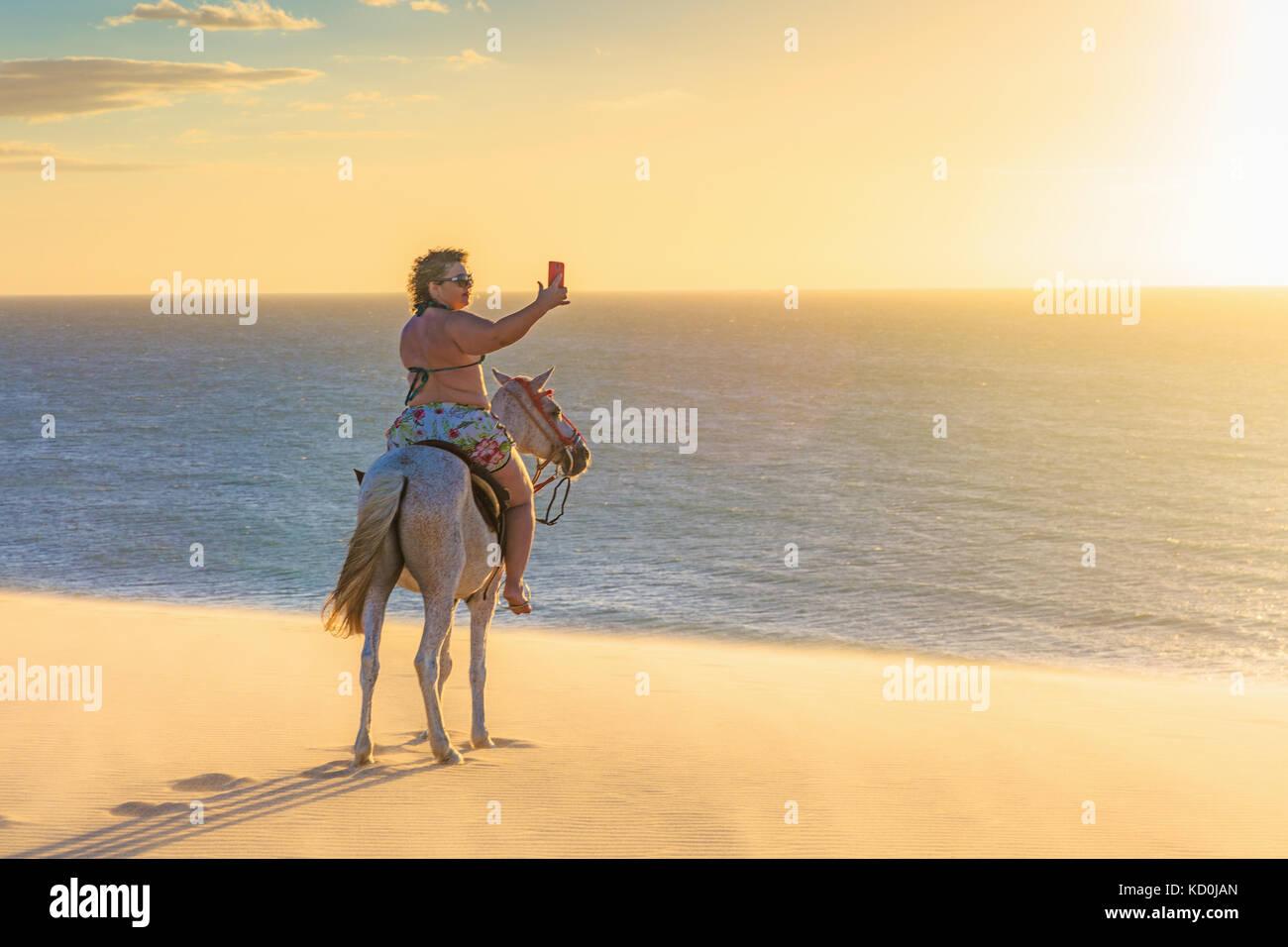Frau Reiten Reiten am Strand, unter der Sie Ihr Smartphone, Jericoacoara, Ceara, Brasilien, Südamerika Stockbild