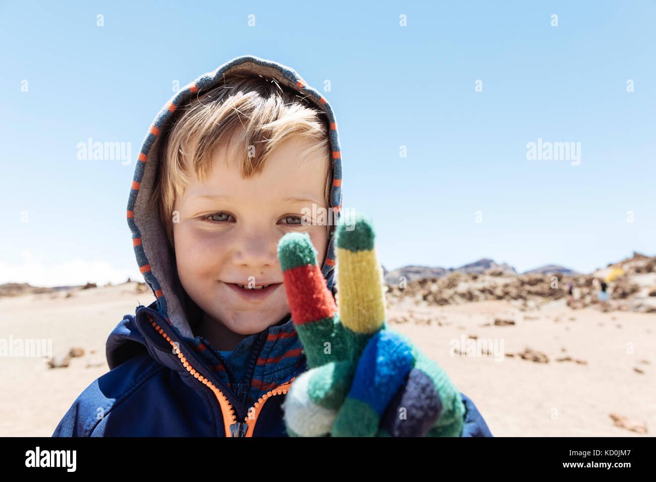 Portrait von cute boy Making Peace Zeichen mit behandschuhten Hand am Mount Teide, Teneriffa, kanarische Inseln Stockbild