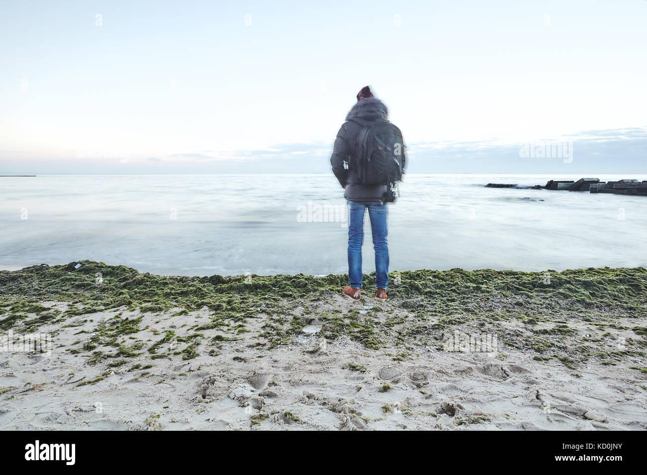 Rückansicht des Menschen am Strand entfernt mit Blick auf das Meer, Odessa, Odessa, Ukraine, Europa Stockbild