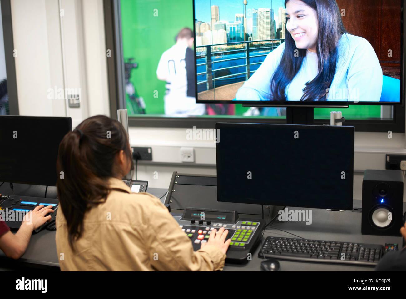Junge männliche und weibliche Studenten am Mischpult watching tv-Bildschirm Stockbild