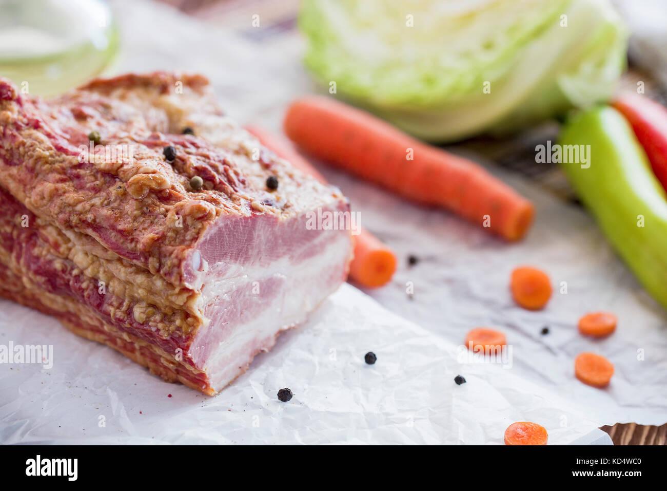 Geräuchertes Fleisch mit Gemüse auf braune Holztisch. geräuchertem rohen geschichtetes Fleisch mit Stockbild