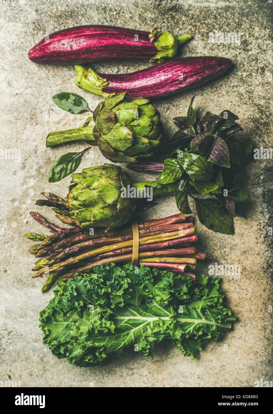 Flachbild-lay von Grün und Violett frisches Gemüse Vielfalt über konkreten Hintergrund, Ansicht von Stockbild