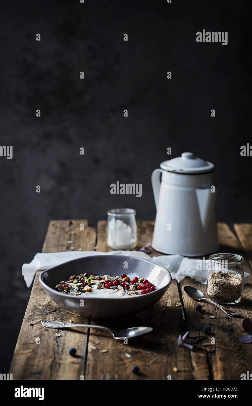 Frühstück auf Holz- Tabelle: Joghurt mit Haferflocken, Samen, Pistazien, Haselnüsse und Johannisbeeren Stockbild