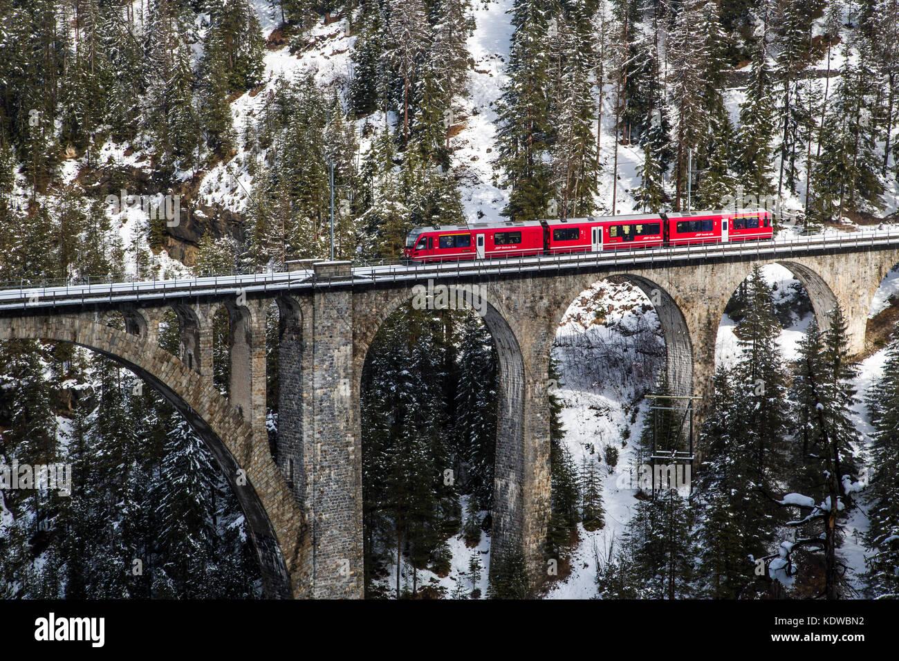 Bernina Express Zug auf wiesener Viadukt von schneebedeckten Wäldern umgeben Davos Albulatal Kanton Graubünden Stockbild