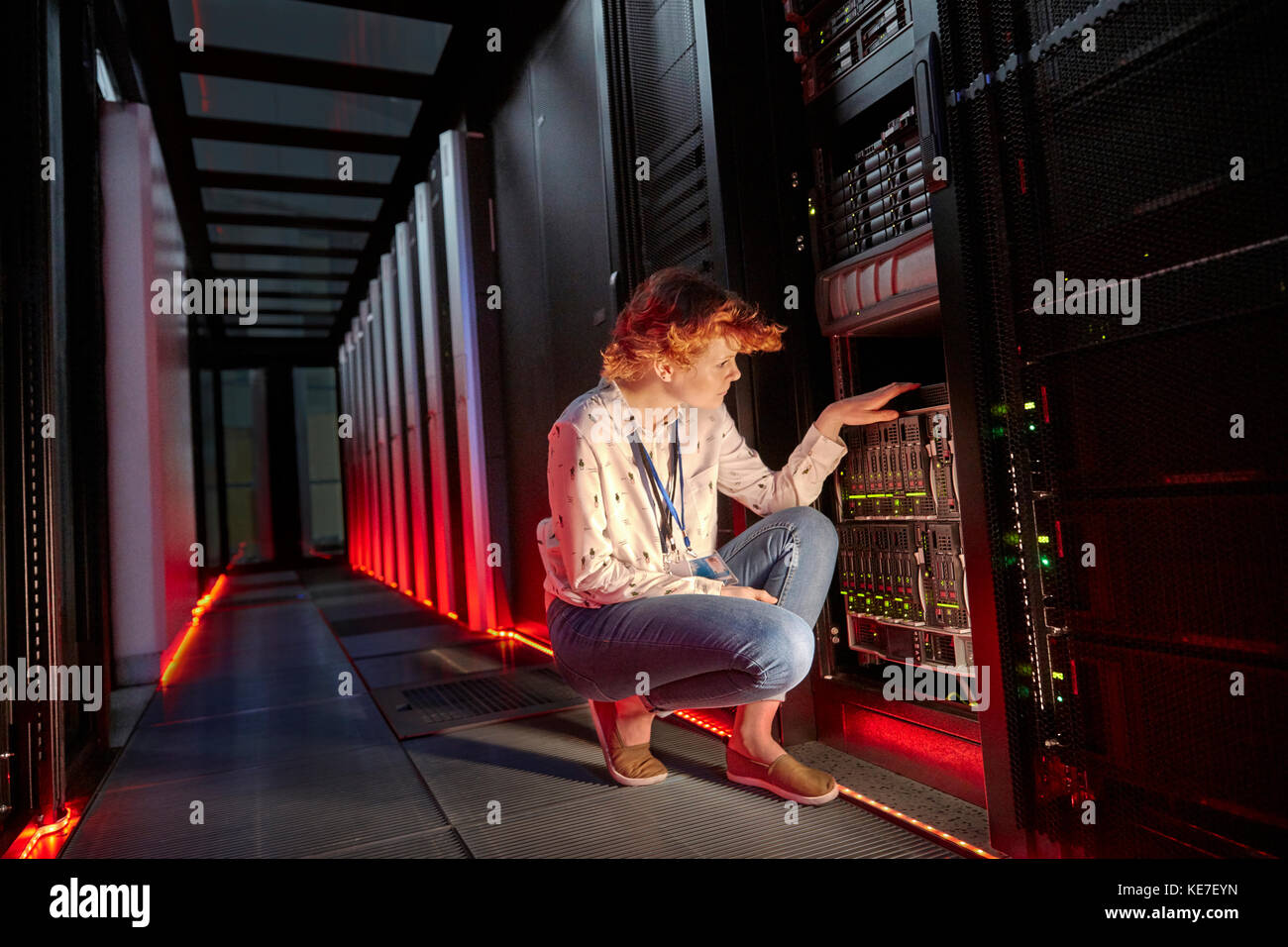 Weibliche it-techniker Prüfung Panel in dunklen Server-Raum Stockbild