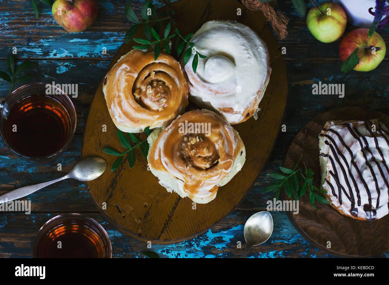 Frisch gebackenen Zimtschnecken mit Zuckerguss, Äpfel und Kaffee auf die schäbigen Hintergrund. Ansicht Stockbild